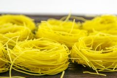 Narrow noodles for cooking on a  wooden base. Narrow, delicious noodles for cooking on a brown wooden base stock image