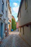 Narrow European street with cobblestone road and medieval architecture, Old Riga Stock Photo