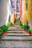 Narrow european street with cobblestone steps and old houses, Po Stock Photography