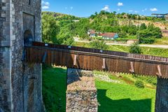 Narrow foot bridge over moat of a medieval castle fort with stone walls stock images