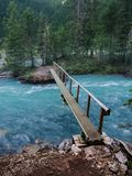 A narrow footbridge crosses over blue glacial water in the Canadian Rockies royalty free stock photography