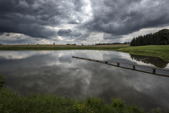 Narrow footbridge to a pond near a forest under storm clouds. In Bohemia Stock Image