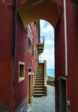 Narrow gate in Manarolo with sea view. A view through a narrow arched gate at a stairway leading up to the house and with the sea at the back. The house is red Royalty Free Stock Photos