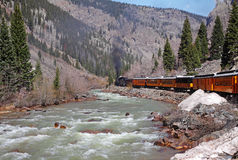 Narrow Gauge Steam Railway in Colorado USA. Narrow Gauge Steam Railway running alongside a river in the Colorado Rockies, USA with melting snow on the riverbank Royalty Free Stock Photos