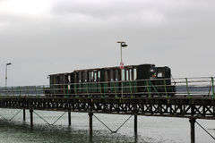 The narrow gauge train that runs the length of the Hythe Pier carrying passengers to and from the ferry boat to Southampton taken. On a dull wet summer`s day royalty free stock photo
