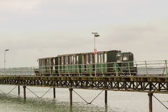 The narrow gauge train that runs the length of the Hythe Pier carrying passengers to and from the ferry boat to Southampton taken. On a dull wet summer`s day Stock Photos