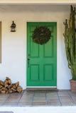Narrow green front door, brown. Front door with holiday wreath Stock Photos