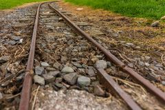 Narrow guage railroad tracks in Agnew Park, Stranraer, Scotland, United Kingdom. Low perspective image of narrow guage railroad tracks for a children`s train in stock photo
