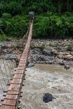 Narrow hängande bro över bergfloden i Himalayas, Nepal, med ett personanseende på det avlägsna slutet av bron. Royaltyfri Fotografi