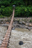 Narrow hanging bridge over mountain river in Himalayas, Nepal, with a person standing at the far end of the bridge. Narrow hanging bridge over fast mountain royalty free stock photography