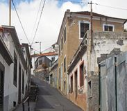 Narrow hillside street in funchal madeira with old Portuguese houses with shutters with a blue sunlit sky. A narrow hillside street in funchal madeira with old stock photography