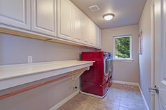 Narrow home laundry with white cabinets and red appliances. Narrow laundry room with long countertop, pure white cabinets and red accent appliances royalty free stock photo
