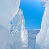Narrow icy glacier crevasse with snow and blue sky Stock Photography