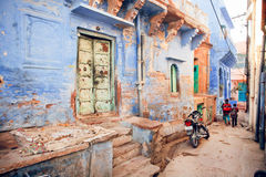 Narrow indian street with blue houses and rushing school children in historical city of India Stock Photos