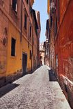 Narrow Italian street in Rome. Narrow Italian street with colorful houses without people on a sunny day Rome, Italy Royalty Free Stock Images