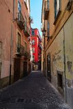 A narrow Italian street in Salerno. A narrow Italian street with shabby walls and a fragment of a bright house with red walls in the distance. City of Salerno Royalty Free Stock Images