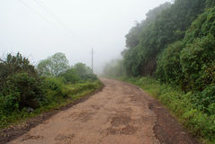A narrow lane leading into fog and mist. A narrow lane in dilapidated condition leading into fog and mist in a hill station Stock Image