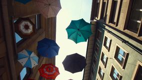 Umbrellas from below in an alley. A narrow lane with lots of culture in Basel stock video