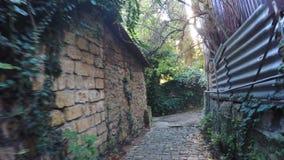 Narrow lane with sun in frame. Down narrow lane mountain village Traffic Cameras stock video