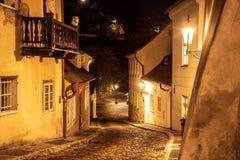 Narrow lappade gatan i gammal medeltida stad med upplysta hus vid tappninggatalampor, Novy svet, Prague, tjeck arkivbilder