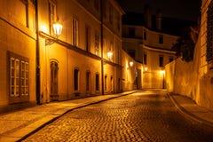 Narrow lappade gatan i gammal medeltida stad med upplysta hus vid tappninggatalampor, Novy svet, Prague, tjeck arkivbild