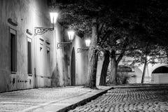 Narrow lappade gatan i gammal medeltida stad med upplysta hus vid tappninggatalampor, Novy svet, Prague, tjeck royaltyfri fotografi