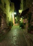 Narrow lappade gatan med blommor i den gamla byn på natten, arkivbilder