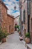 Narrow lappade gatan med blommor i den gamla byn Tourrettes royaltyfri fotografi