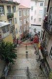 Narrow lappade gatan med moment i Lissabon Arkivfoton