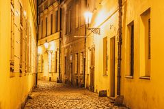 Narrow lappade gatan som var upplyst vid gatalampor av den gamla staden, Prague, Tjeckien royaltyfri fotografi