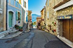 Narrow lappade gator med blommor i den gamla byn Gourdon, royaltyfri foto