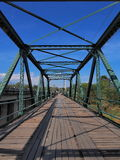 Narrow long bridge with symmetrical metal structure Royalty Free Stock Images