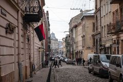 Narrow Lviv street with combat Ukrainian flag Stock Photos