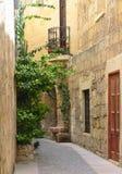 Narrow maltese street. Narrow street and typical house on Gozo island, Malta Royalty Free Stock Photo