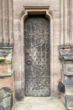 Narrow Medieval oak door. With original rusting metal leaf pattern, square head nails, and door handle Stock Photography