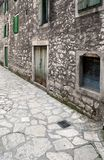 Narrow medieval street. Detail of medieval, mediterranean town with decaying, dirty stonework and wooden windows and doors Åibenik, Croatia stock images