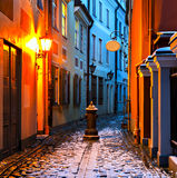 Narrow medieval street in old Riga city at winter night Stock Photos