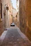 Narrow medieval street with stone houses in Mdina, Malta Royalty Free Stock Images