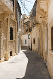 Narrow medieval street with stone houses in Mdina, Malta Stock Photography