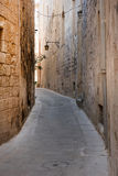 Narrow medieval street with stone houses in Mdina, Malta Stock Images