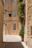 Narrow medieval street with stone houses in Mdina, Malta Stock Photos