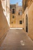 Narrow medieval street with stone houses in Mdina, Malta Stock Photo