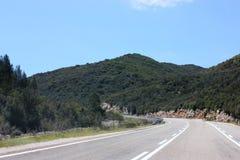 Narrow mountain asphalt road. Blue summer sky Stock Image
