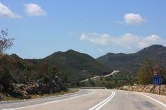 Narrow mountain asphalt road. Blue summer sky Royalty Free Stock Image