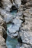 Narrow  mountain stream flows among blue striped r Royalty Free Stock Image