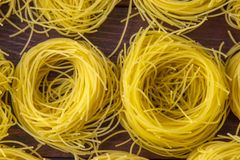 Narrow noodles for cooking on a  wooden base. Narrow, delicious noodles for cooking on a brown wooden base royalty free stock photos