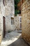 Narrow old street in stone, Croatia Stock Photos