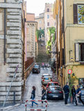 The narrow old streets of ancient Rome between the houses with stairs and tourists who walk through it considering attractions Stock Images
