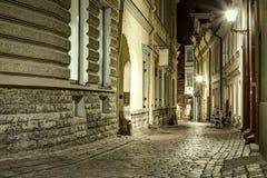 Narrow old town street of Tallinn, Estonia at night time. Stone stock photo