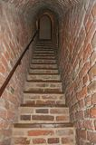 Narrow passage made of bricks with stairs inside the walls of the medieval Ammersoyen Castle. Ammersoyen, southern Netherlands - July 01, 2017. Narrow passage Stock Photo